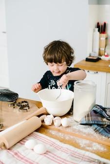 Ragazzino in cucina che aiuta a cucinare la pasta per la cottura