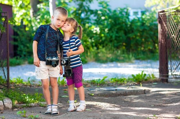 Ragazzino e una bambina con due macchine fotografiche d'epoca