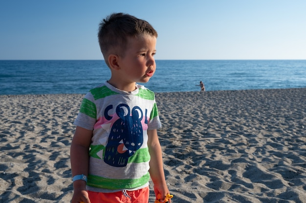 Ragazzino che cerca sua mamma sulla spiaggia.