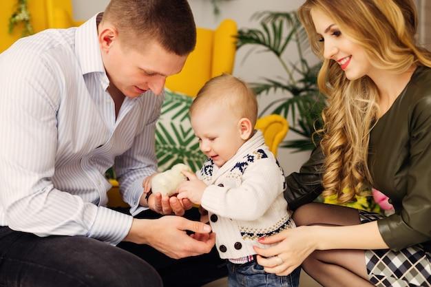 Il bambino guarda il pollo nelle mani del padre e la mamma si siede accanto a loro nella bellissima stanza con una sedia gialla