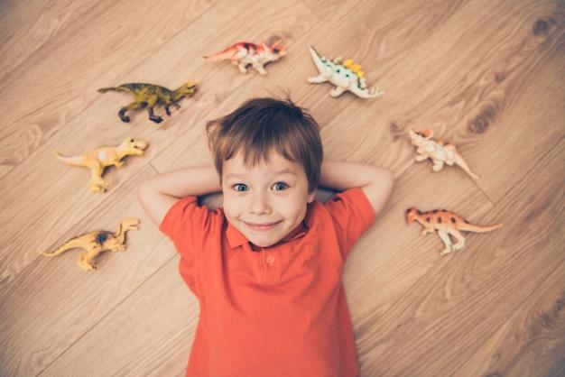Ragazzino sdraiato sul pavimento con una collezione di dinosauri. messa a fuoco selettiva