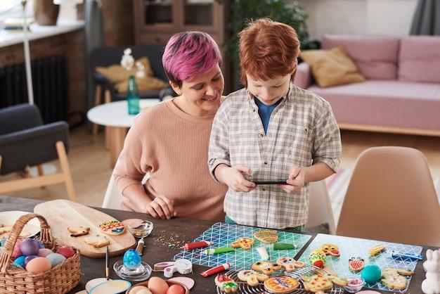Ragazzino che fa foto al telefono del suo mestiere mentre decora i biscotti di pan di zenzero insieme a sua madre
