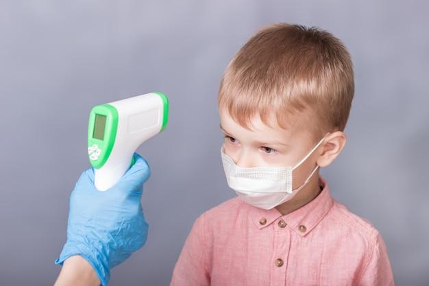 Il ragazzino misura la temperatura con un termometro