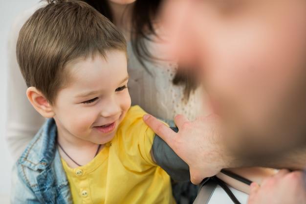 Visita medica del ragazzino - medico che misura la pressione sanguigna di un bambino
