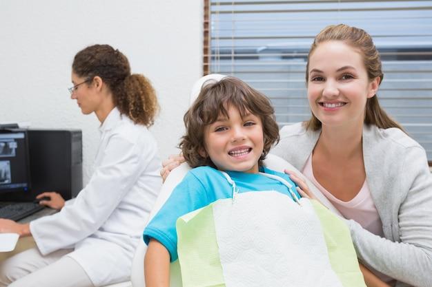 Ragazzino e madre che sorridono alla macchina fotografica con il dentista nella priorità bassa