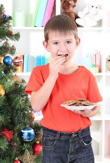 Il ragazzino vicino all'albero di natale mangia i biscotti