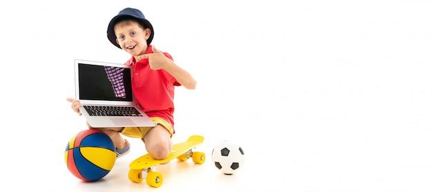 Un bambino in panama, maglia gialla, pantaloncini rossi e scarpe da ginnastica bianche è in piedi sui polpacci su un penny giallo con palloni da basket e da calcio e un computer portatile