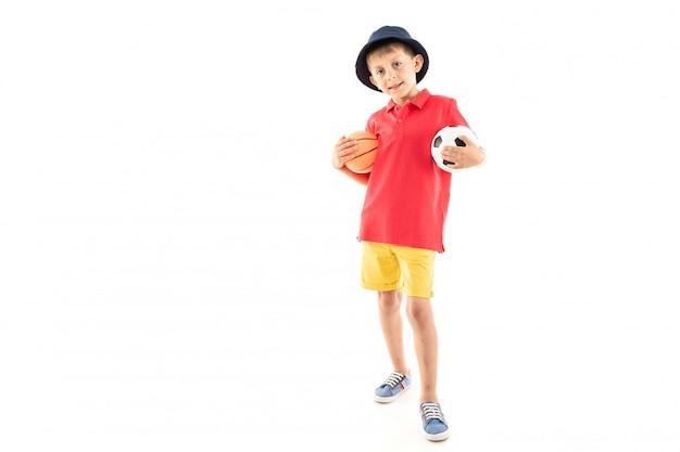 Un bambino in panama, maglia gialla, pantaloncini rossi e scarpe da ginnastica bianche sta con palloni da basket e da calcio