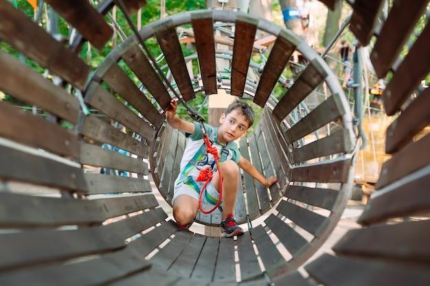Un ragazzino supera l'ostacolo nel parco avventura