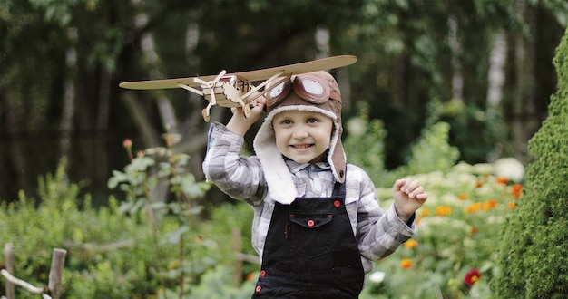 Ragazzino con cappello da pilota che gioca con un aereo di legno bambino felice che tiene in mano un aeroplano giocattolo