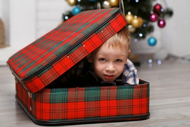 Ragazzino che gioca a nascondersi in una valigia scozzese rossa all'interno con decorazioni natalizie
