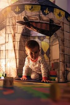 Ragazzino che gioca nel giocattolo del castello a casa. concetto di infanzia.