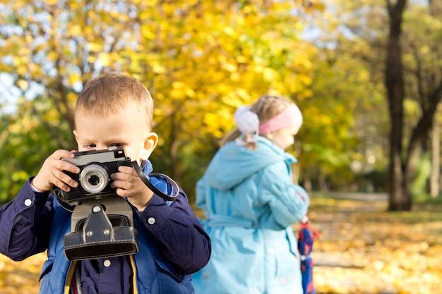 Ragazzino che gioca nel parco con sua sorella che prova una retro macchina fotografica