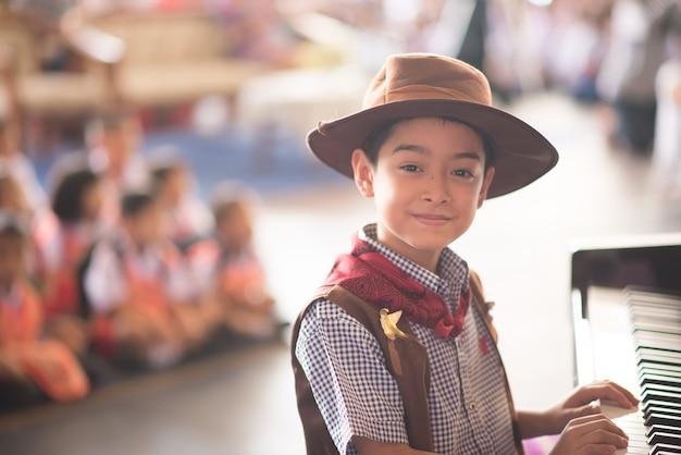 Little boy suonare il pianoforte performance all'aperto