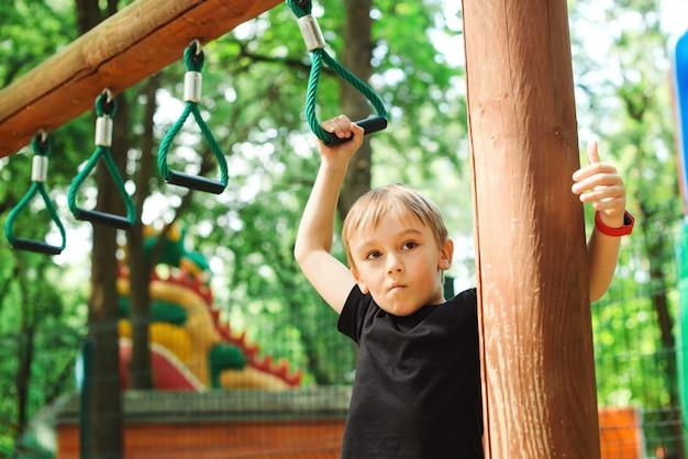 Ragazzino che gioca al parco avventura di corda. il ragazzo che fa la tirata aumenta sul campo da giuoco della corda all'aperto.