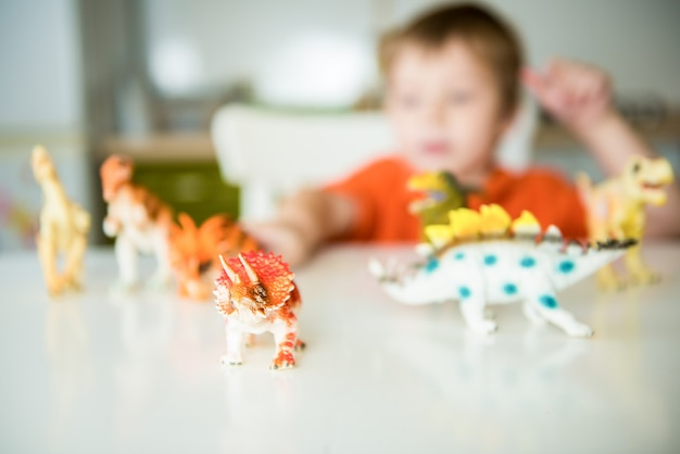 Ragazzino che gioca con i dinosauri. collezione di lucertole, messa a fuoco selettiva