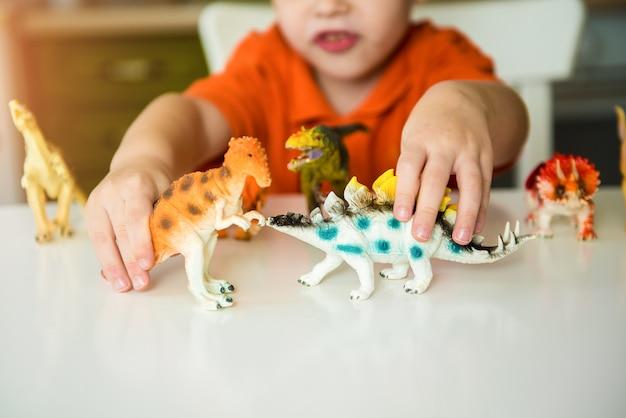 Ragazzino che gioca con i dinosauri. collezione di lucertole