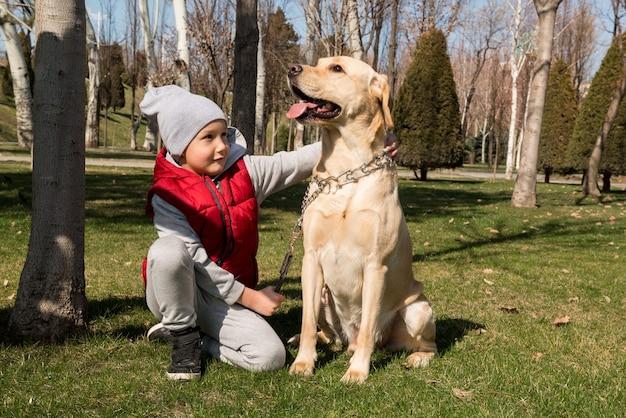 Ragazzino che gioca con il cane labrador nel parco di primavera