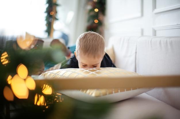 Ragazzino che gioca con un cuscino, si nasconde dietro di esso, sorride e si diverte in un ambiente natalizio.