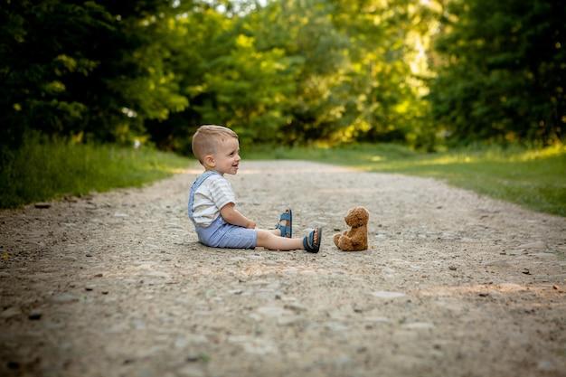 Ragazzino che gioca con l'orsacchiotto di peluche sul sentiero.