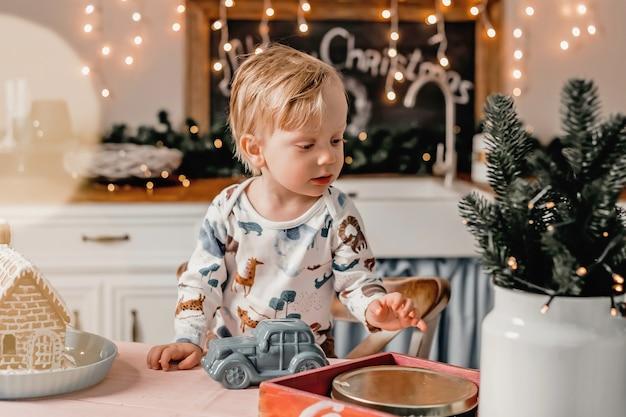 Il ragazzino gioca in cucina con l'arredamento di capodanno. il passatempo dei bambini in quarantena