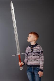 Un ragazzino posa con una spada in uno studio fotografico su uno sfondo grigio