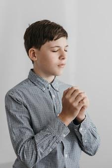 Ragazzino che prega al chiuso