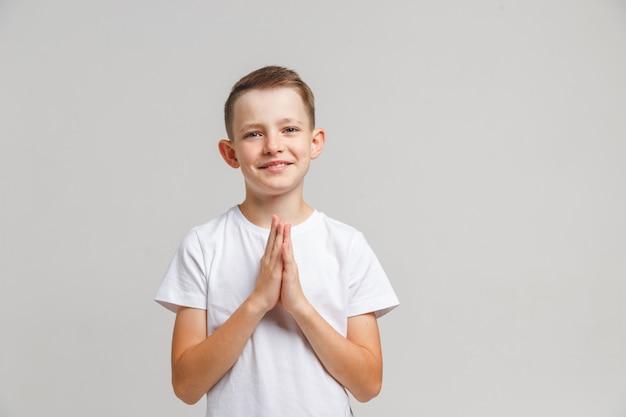 Pregare del ragazzino isolato sul bianco