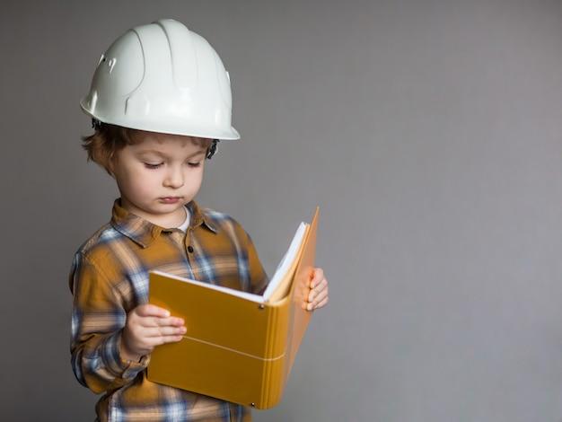 Ragazzino in casco protettivo, bambino con capanna di ingegneria, edificio in via di sviluppo costruzione e concetto di architettura