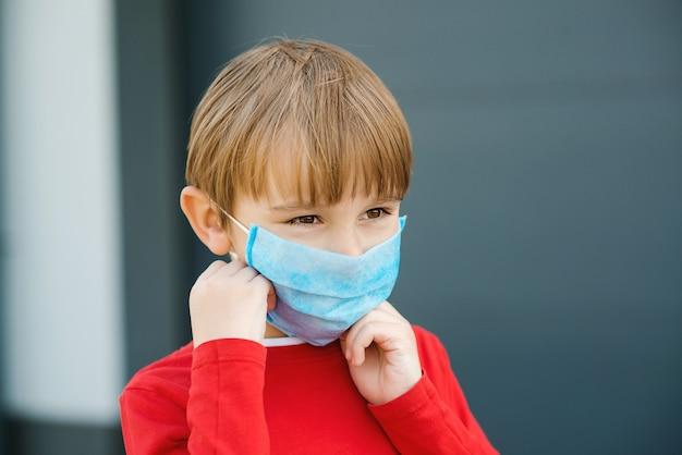 Ragazzino che mette sulla maschera protettiva del fronte all'aperto. epidemia di coronavirus.