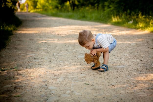 Il ragazzino solleva l'orsacchiotto sul sentiero per pedoni.