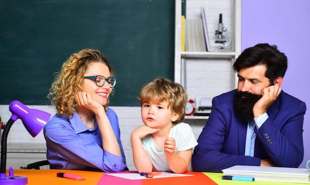 Ragazzino pronto a studiare il bambino dello studente elementare della scuola elementare con i genitori dei genitori