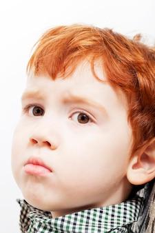 Ragazzino in capelli rossi con un'espressione facciale frustrata