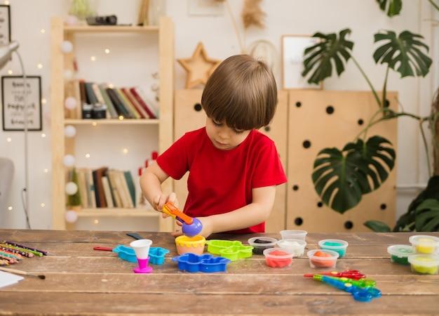 Un ragazzino in una maglietta rossa gioca con la plastilina sul tavolo di legno nella stanza. sviluppo delle capacità motorie fini.