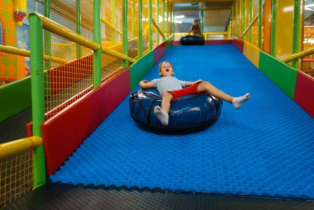 Il ragazzino cavalca su tubi, parco giochi nel centro di intrattenimento. area giochi interna, sala giochi