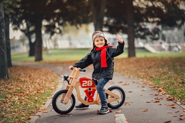 Ragazzino che guida una bici dell'equilibrio in città in autunno