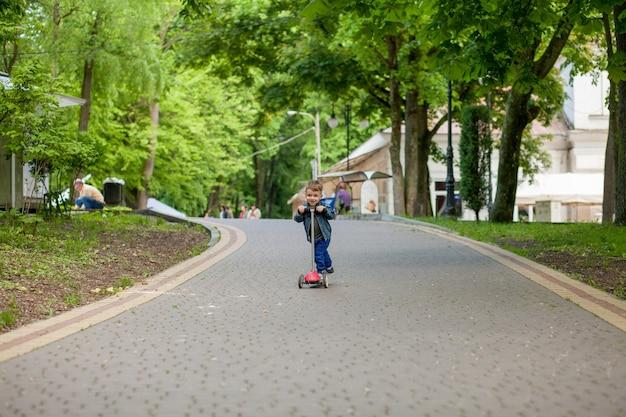 Little boy in sella a scooter nel parco cittadino in estate. sport per bambini all'aperto. bambino felice che gioca con il suo scooter. il bambino impara a guidare lo scooter nel parco. infanzia felice.