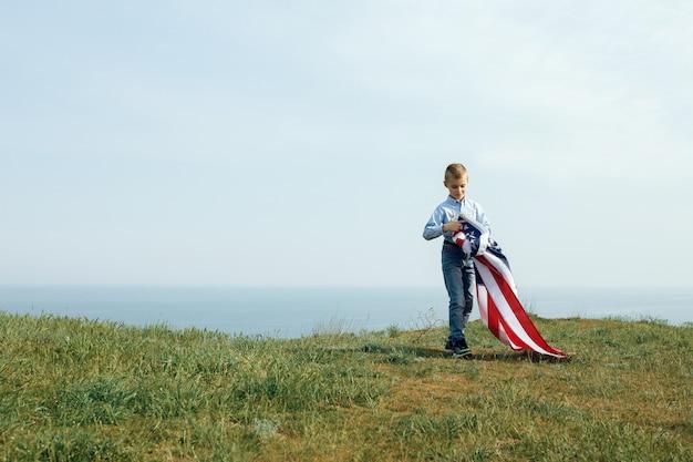 Un ragazzino corre con la bandiera degli stati uniti. 4 luglio festa dell'indipendenza.