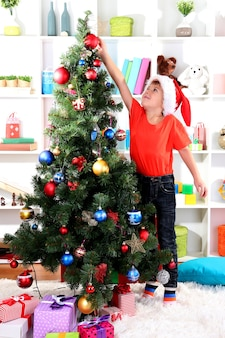Il ragazzino con il cappello di babbo natale decora l'albero di natale in camera