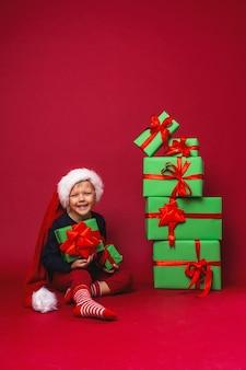 Il ragazzino in cappello della santa si siede accanto ai contenitori di regalo di natale della piramide sul rosso in studio.