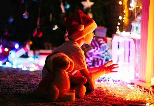 Ragazzino con cappello da babbo natale seduto a casa su una superficie natalizia