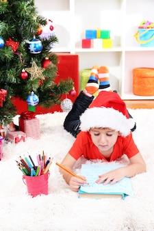 Il ragazzino con il cappello di babbo natale scrive una lettera a babbo natale