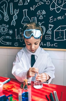 Scienziato del ragazzino che estrae liquido dal pallone contro la lavagna con disegni