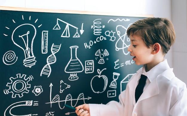 Scienziato del ragazzino che mostra il disegno matematico sulla lavagna con un pennarello