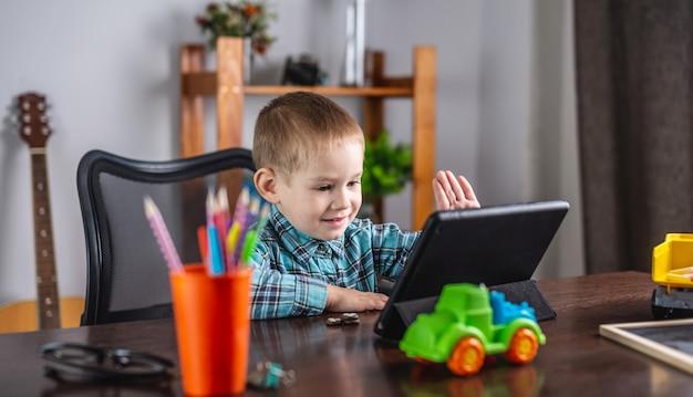 Il ragazzino in una camicia sta guardando lo schermo del tablet e agitando