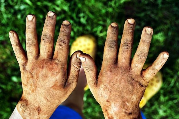 Ragazzino che mostra le sue mani sporche dopo aver giocato con un'argilla all'aperto