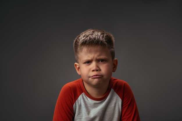 Ragazzino che mostra con la sua faccia non mi piace ai suoi genitori isolati su sfondo grigio