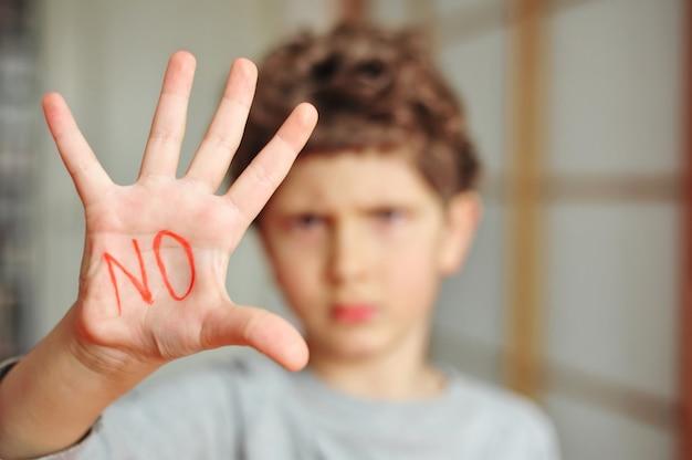 Un ragazzino mostra una palma con un'iscrizione proibitiva n