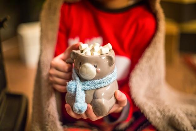 Il ragazzino si siede vicino a un albero di natale e tiene una tazza di cacao con marshmallow