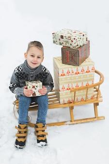 Ragazzino, seduto sulla slitta di legno, decorato con scatole con regali di natale